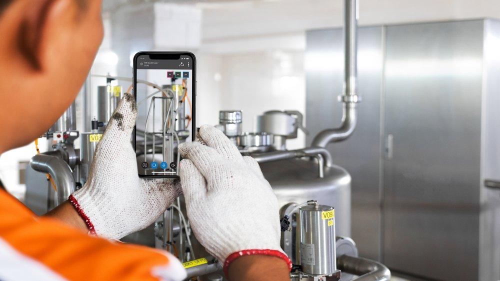 Remote AR-Lösung von Eriks, Maschine wird durch Smartphone-Display geprüft